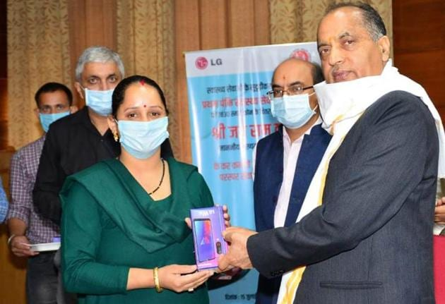 Chief minister Jai Ram Thakur giving an ASHA worker a smart phone in Shimla on Wednesday.(HT Photo)