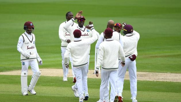 Jason Holder and Roston Chase celebrate the wicket of Zak Crawley of England with teammates during Day One of the 2nd Test Match in the #RaiseTheBat Series between England and The West Indies at Emirates Old Trafford on July 16, 2020 in Manchester, England.(Getty Images for ECB)