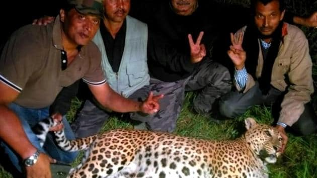 Hunters posing with the leopard they shot dead in Almora.(HT Photo)