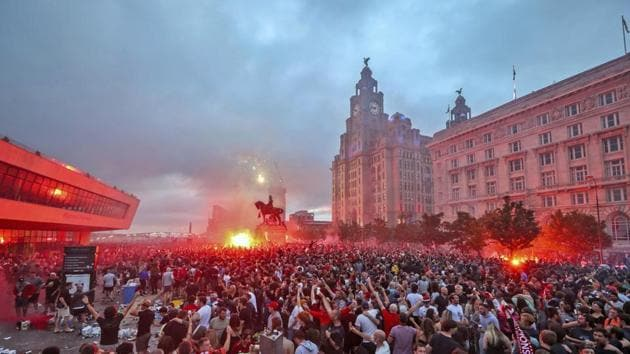 Liverpool fans let off flares outside the Liver Building in Liverpool, Friday June 26, 2020, as Liverpool soccer fans gather and celebrate for the team clinched the English Premier League title.(AP)