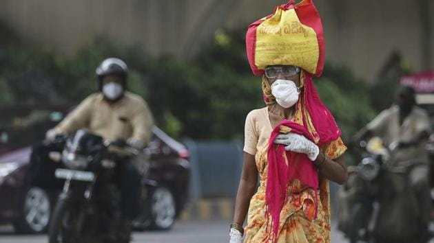 A woman wearing a face mask walks on a street in Hyderabad. India crossed 1 million coronavirus cases on Friday, third only to the United States and Brazil, prompting concerns about its readiness to confront an inevitable surge that could overwhelm hospitals and test the country's feeble health care system.(AP)