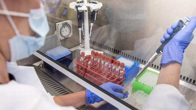 In this handout photo released by the University of Oxford samples from coronavirus vaccine trials are handled inside the Oxford Vaccine Group laboratory in Oxford.(AP)