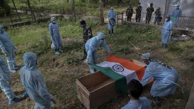 Indian paramilitary soldiers cover the coffin of their colleague who died of Covid-19, at a crematorium in Srinagar.(AP)