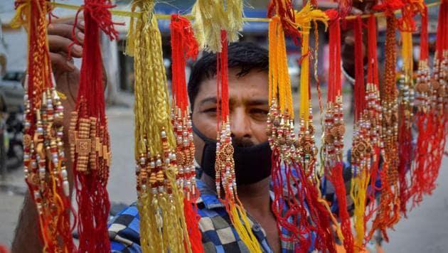 A vendor arranges rakhis put on display for sale, ahead of the Raksha Bandhan festival, at his roadside shop, in Prayagraj, Tuesday, July 21, 2020. (Representational)(PTI)