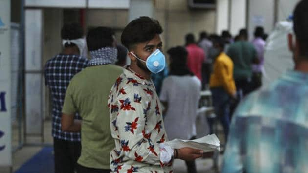 A man wearing a face mask waits to consult a doctor at a Covid-19 screening centre at a government-run hospital in Jammu.(AP File Photo)