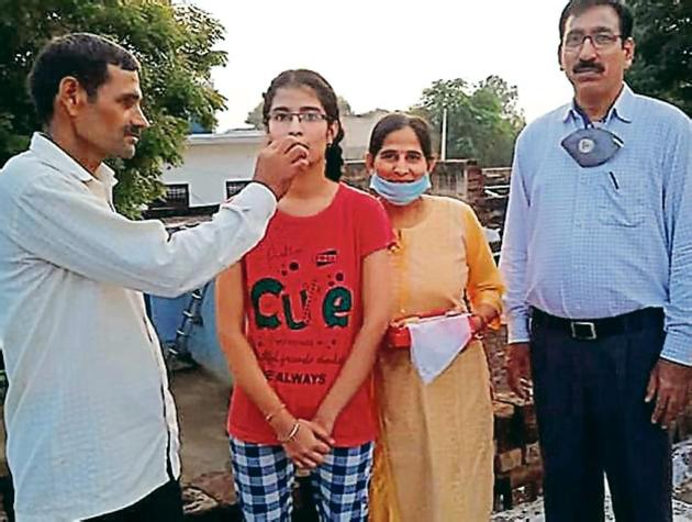 Manisha of Government Senior Secondary School in Mahendergarh's Sihma celebrates with her kin after securing 499 marks out of 500.(HT)