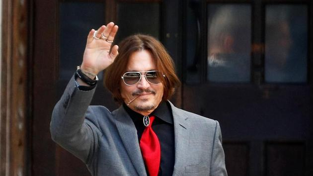 Actor Johnny Depp waves as he leaves the High Court in London.(REUTERS)