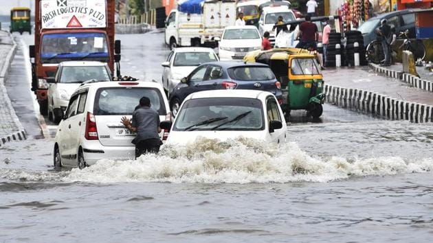 Commuters wade through a waterlogged road after heavy rain, at NH 24 near Mayur Vihar 2, in New Delhi, India, on Wednesday, July 22, 2020.(Ajay Aggarwal /HT Photo)