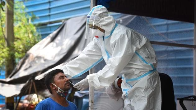 A health worker wearing PPE coveralls collects swab samples to test for coronavirus infection.(Sanchit Khanna/HT PHOTO)