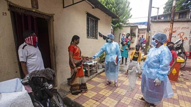 Health workers check a woman's blood oxygen levels using a pulse oximeter during a door to door screening for coronavirus in a slum near Dandekar Bridge in Pune, Maharashtra.(Pratham Gokhale/HT Photo)