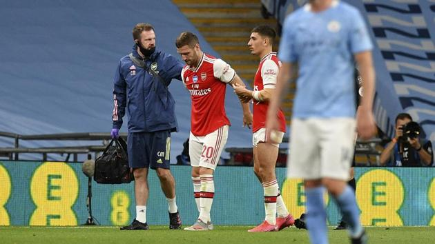 Arsenal's Shkodran Mustafi is assisted from the field during the FA Cup semifinal soccer match between Arsenal and Manchester City at Wembley in London.(AP)