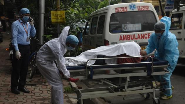 Medical professionals in PPE coveralls carry a suspected coronavirus patient on a stretcher at Beckbagan on day one of weekly two day complete lockdown imposed by the state government to check the spread of coronavirus (COVID - 19) disease, in Kolkata, West Bengal.(Samir Jana / Hindustan Times)