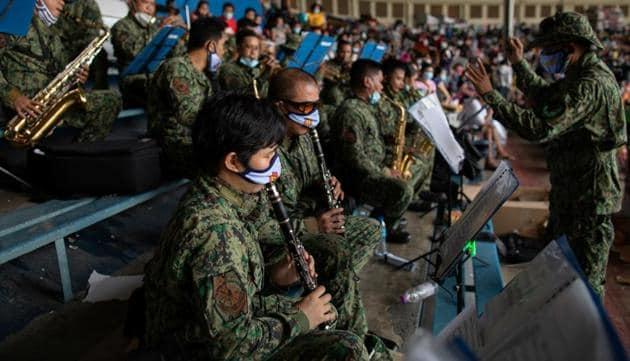 Members of the Philippine National Police wearing masks for protection against the coronavirus disease (COVID-19), play music inside a baseball stadium where thousands of stranded Filipinos wait to be transported back to their provinces through a government transportation program, in Rizal Memorial Sports Complex.(REUTERS)