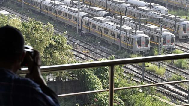 A man photographs Delhi Metro yellow line trains parked at Khyber Pass Metro Depot, in New Delhi.(Ajay Aggarwal /HT PHOTO)