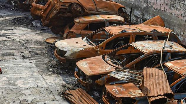 A man walks past the charred remains of vehicles set ablaze by rioters at parking during the anti-CAA protests in February, at Shiv Vihar area of Northeast Delhi.(PTI)