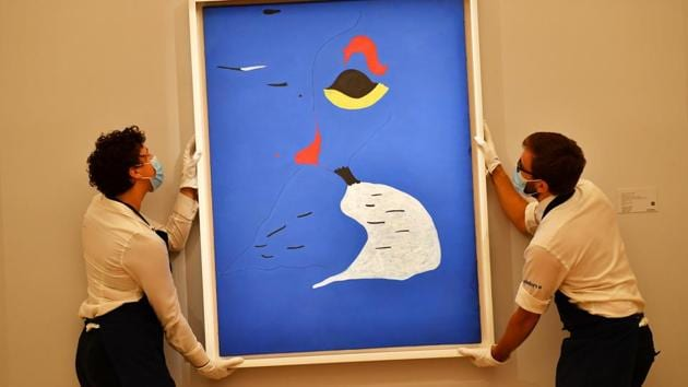 Gallery assistants pose with 'Peinture (Femme Au Chapeau Rouge)' by Spanish artist Joan Miro during a media preview for 'Rembrandt to Richter' at Sotheby's auction house in London, Britain, July 23 2020.(REUTERS/Dylan Martinez)