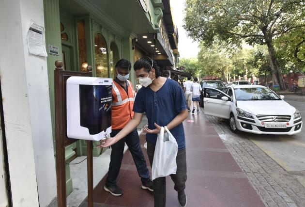 In unlock 3.0, a visitor uses a hand sanitising dispenser before entering a restaurant in Delhi's Khan Market.(Photo: Sanjeev Verma/HT)