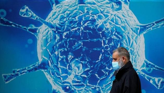 A man wearing a protective face mask walks past an illustration of a virus outside a regional science centre, as the city and surrounding areas face local restrictions in an effort to avoid a local lockdown being forced upon the region, amid the coronavirus disease (COVID-19) outbreak, in Oldham, Britain August 3, 2020. (Representational)(REUTERS)
