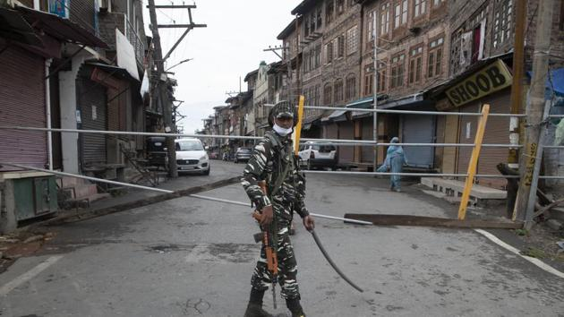 An Indian paramilitary soldier stands guard by a closed road, as Kashmiris marked Eid during lockdown to curb the spread of coronavirus in in Srinagar.(AP)
