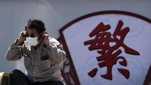"""A man puts on his face mask to protect against the new coronavirus as he sits on a tricycle cart passing by the words """"Complicated"""" on a street in Beijing.(AP)"""