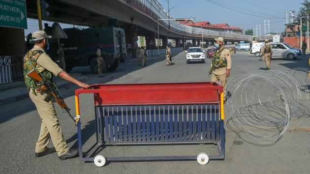 Security personnel place a barricade on a street during the restrictions imposed on the first anniversary of revocation of the special status of Jammu and Kashmir, in Srinagar on Wednesday.(PTI Photo)