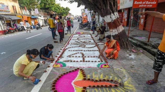 Children and youngsters make 'rangoli' on pavement along a road, on the eve of the groundbreaking ceremony of the Ram Mandir, in Ayodhya.(PTI)