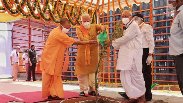 Prime Minister Narendra Modi along with Uttar Pradesh Chief Minister Yogi Adityanath waters Parijaat sapling ahead of the inception of Bhoomi Pujan for the construction of Ram Temple, in Ayodhya.(PTI)