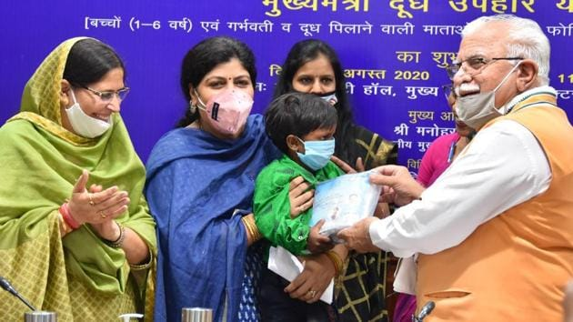 Haryana chief minister Manohar Lal distributing milk powder to a beneficiary in Chandigarh on Wednesday.(HT PHOTO)
