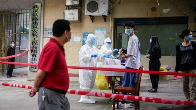 Medical workers in protective suits conduct nucleic acid testings for residents at a residential compound in Wuhan.(Reuters File Photo)