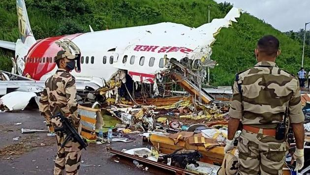 Army personnel stand guard at the site of the wreckage of the Air India Express flight at Kozhikode International Airport in Karipur on Saturday. 18 people including two pilots were killed when the Dubai-Kozhikode Air India flight crash landed at Kozhikode on Friday night.(ANI PHOTO.)