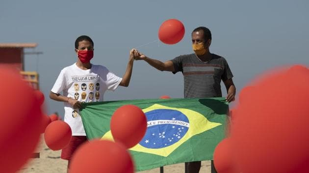Marcio Antonio do Nascimento, right, and Lucas Cruz, the father and brother of 25-year-old Hugo do Nascimento who died from the new coronavirus, hold a Brazilian national flag as red balloons are released to honor the victims of Covid-19.(AP)
