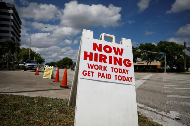 """A """"Now Hiring"""" sign advertising jobs at a hand car wash is seen along a street, as the spread of the coronavirus disease (Covid-19) continues, in Miami, Florida, US.(REUTERS)"""