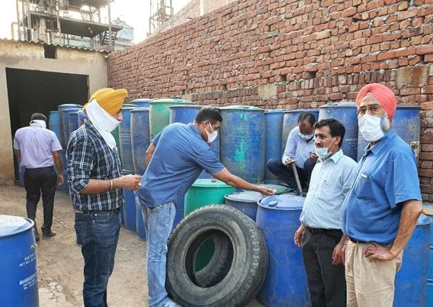 Excise officials check drums containing illicit chemicals at a unit in Dera Bassi in Mohali on Sunday.(HT Photo)