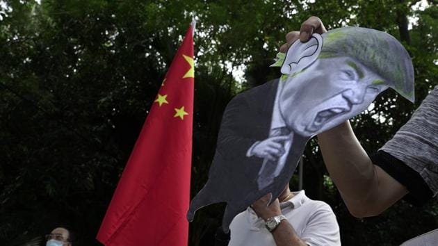 Pro-China supporters display a picture of US President Donald Trump during a protest against the US sanctions outside the US Consulate in Hong Kong.(AP)