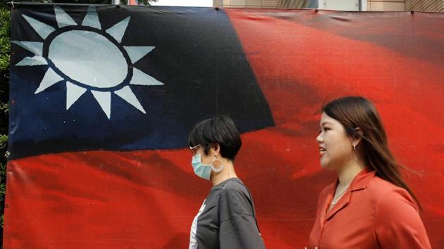 People walk past a Taiwanese flag amid the coronavirus disease (Covid-19) pandemic in Taipei, Taiwan.(Reuters Photo)