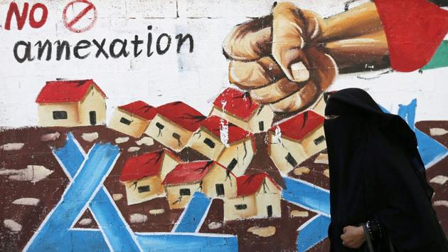 A Palestinian woman walks past a mural against Israel's plan to annex parts of the Israeli-occupied West Bank, in Rafah in the southern Gaza Strip.(REUTERS)