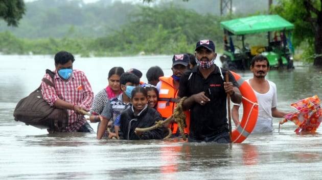 Rescuers lead a group of people to safety in Warrangal in Telangana.(Sourced)