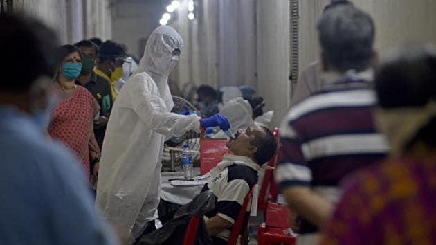 Health care staff collect swab sample of the residents of Omkar SRA at Malad(E) during Covid-19 pandemic in Mumbai.(Satyabrata Tripathy/HT Photo)