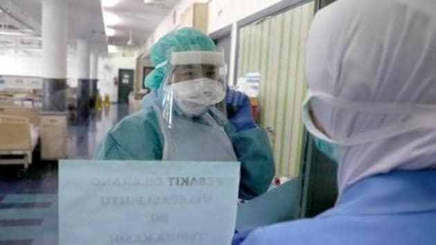 Nurses talk to each other through a glass at the coronavirus disease (COVID-19) ward at Kuala Lumpur Hospital, in Kuala Lumpur, Malaysia.(Reuters)