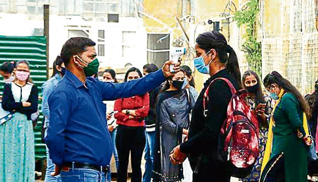 A staff member checking the body temperature of a student at RKMV College, Shimla, on Monday.(Deepak Sansta / HT)