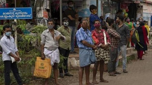 People wearing masks as a precaution against the coronavirus disease wait for transportation in Kochi, Kerala.(AP Photo)