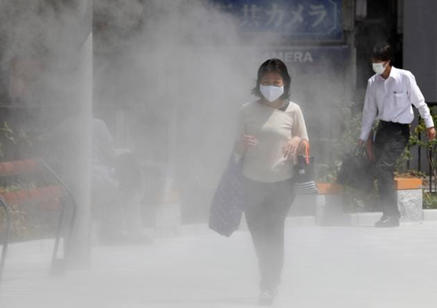 A woman wearing a protective mask walks through a cooling mist in the hot weather, amid the coronavirus disease (COVID-19) pandemic in Tokyo, Japan August 18, 2020.(REUTERS)