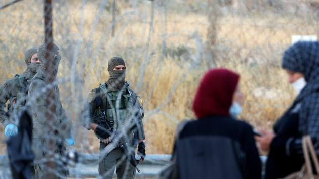 Members of Israeli security forces stand guard as Palestinian labourers gather near an Israeli checkpoint.(REUTERS/Representative Image)