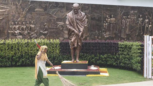 A worker sweeps an area near a statue of Mahatma Gandhi inside the Rashtriya Swachhata Kendra, an interactive experience centre on the Swachh Bharat Mission, at Rajghat in New Delhi.(PTI)