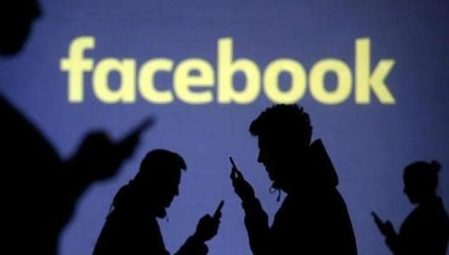 Silhouettes of mobile users are seen next to a screen projection of Facebook logo.(Reuters File Photo)