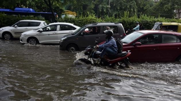 Vehicles cross a waterlogged stretch in Delhi.(Mohd Zakir/HT Photo)