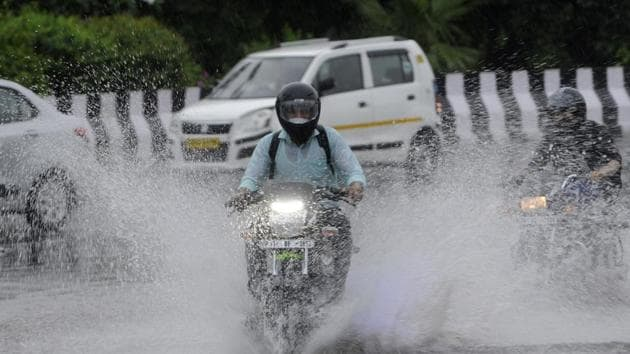 A motorcyclist passes through a heavily waterlogged stretch of road, at Sector 95, in Noida on Wednesday.(Sunil Ghosh/HT Photo)