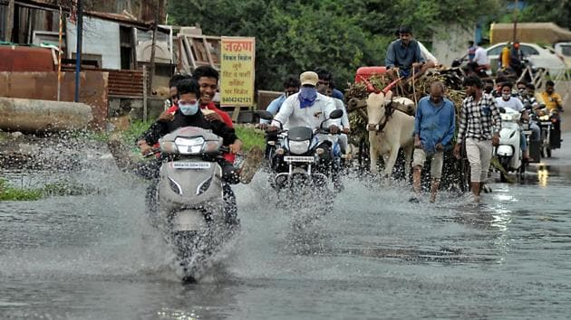 Local people wade submerged bank side area road during Krishna river flooding after heavy rain in catchment area of Koyana dam in Sangli on Tuesday(Uday Deolekar/HT Photo)