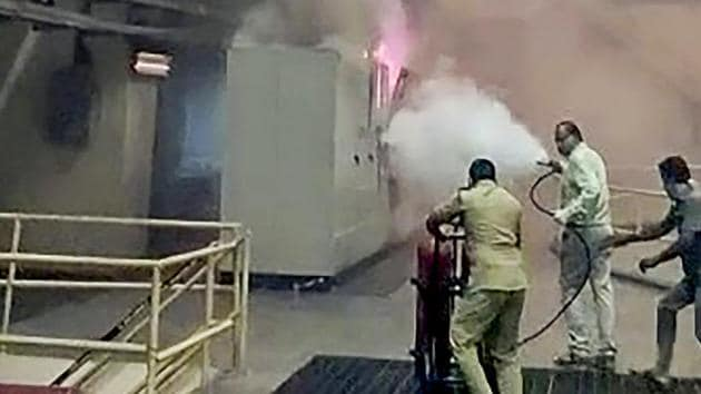 Employees use a fire extinguisher as they attempt to douse a fire at Srisailam hydroelectric plant, in Telangana on Friday.(PTI Photo)