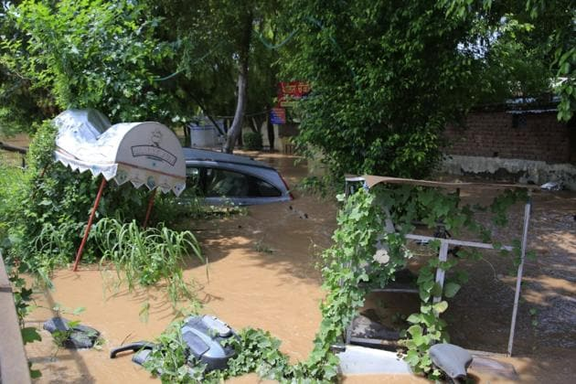 Cars, scooters and a cart under water near the Baltana police chowki after heavy rains in the region.(Keshav Singh/HT)